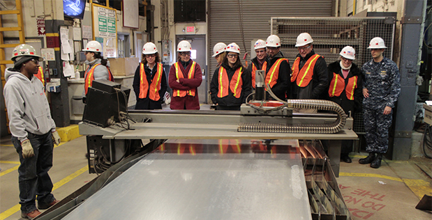 DARPA MENTOR2 performers observe current industrial-scale laser cutting at Norfolk area industrial Ship Yards. The Fab Lab installation at the Mid-Atlantic Regional Maintenance Center will include a smaller laser cutter and other prototyping equipment. Na