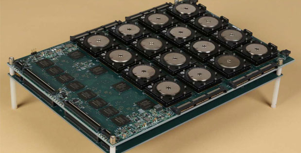 A circuit board shows 16 of the new brain-inspired chips in a 4 X 4 array along with interface hardware. The board is being used to rapidly analyze high-resolutions images. Courtesy: IBM