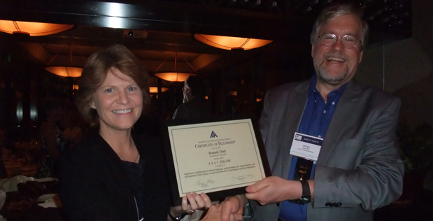 Bonnie Dorr (left), program manager in DARPA's Information Innovation Office (I2O), shakes hands with Henry Kautz, past president of the Association for the Advancement of Artificial Intelligence (AAAI), upon her recent induction as an AAAI Fellow.
