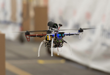 A FLA quadcopter self-navigates around boxes during initial flight data collection using only onboard sensors/software. DARPA's FLA program aims to develop and test algorithms that could reduce the amount of processing power, communications, and human intervention needed for unmanned aerial vehicles (UAVs) to accomplish low-level tasks, such as navigation around obstacles in a cluttered environment