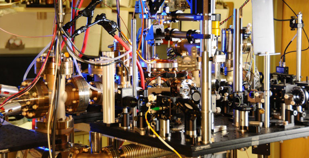 QuASAR atomic clock. Ytterbium atoms are generated in an oven (cylinder on left) and sent to a vacuum chamber (center) to be manipulated and probed by lasers. Courtesy: NIST