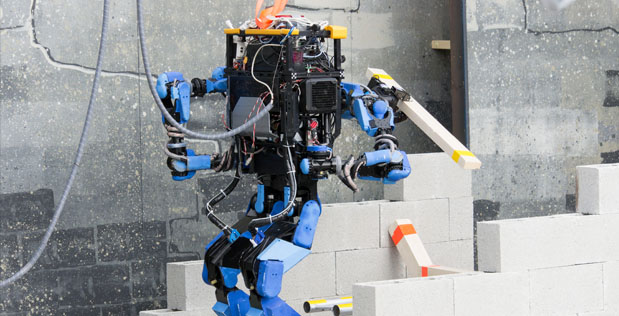 Team SCHAFT's robot, S-One, clears debris at the DRC Trials.
