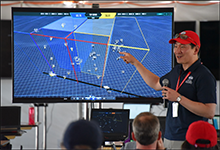 Image Caption: Timothy Chung, DARPA program manager, explains a real-time data visualization system used for the Service Academies Swarm Challenge. The system tracks the simultaneous flight of dozens of unmanned aerial vehicles (UAVs) demonstrating autonomous tactics designed by Cadets and Midshipmen at the U.S. Military Academy, the U.S. Naval Academy, and the U.S. Air Force Academy. The three-day experiment had the Service academy teams compete in a modified version of capture the flag, with the Naval Academy taking home top honors. Click below for high-resolution image.