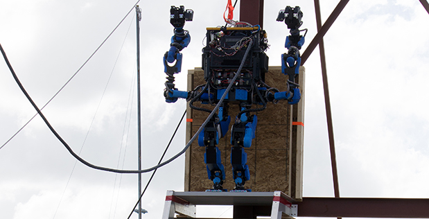 Team SCHAFT raises the arms of its S-One robot in victory after successfully completing the Climb Industrial Ladder task at the DRC Trials. SCHAFT won that task and three others, and scored the most points of any team at the event.
