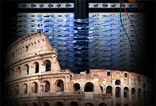 "Image Caption: In this photo illustration, a few dozen of the 256 software defined radio units, which comprise the heart of DARPA's Colosseum—the world's largest ""channel emulator"" for simulating electromagnetic communication in different peacetime and contested contexts—rise up from the original Roman Colosseum after which the electronic testbed is named. Click on image below for high-resolution."